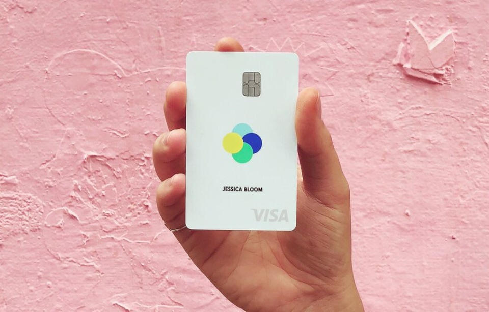 Picture of a woman holding the Petal Visa card